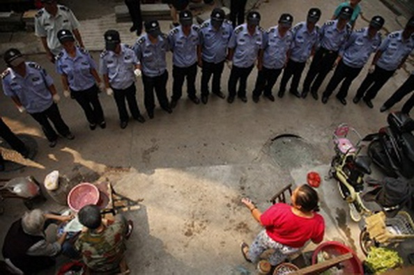 A line of urban management officers, known as chengguan, stare in silence at an illegal vegetable vendor in Wuhan, central Chinas Hubei province, 19 September 2012.The urban management officers, known as chengguan, started to conduct a new way to enforce laws in Wuhan, central Chinas Hubei province this Wednesday (19 September 2012). Previously, the execution of duties adopted by such officers was heavily criticized as oppressive across China. But this time instead of physical and verbal enforcement, the squad stared in silence at those who dared to violate the laws. Surprisingly, this novel execution has received satisfactory results as the officers have succeeded in making illegal vendors behave.